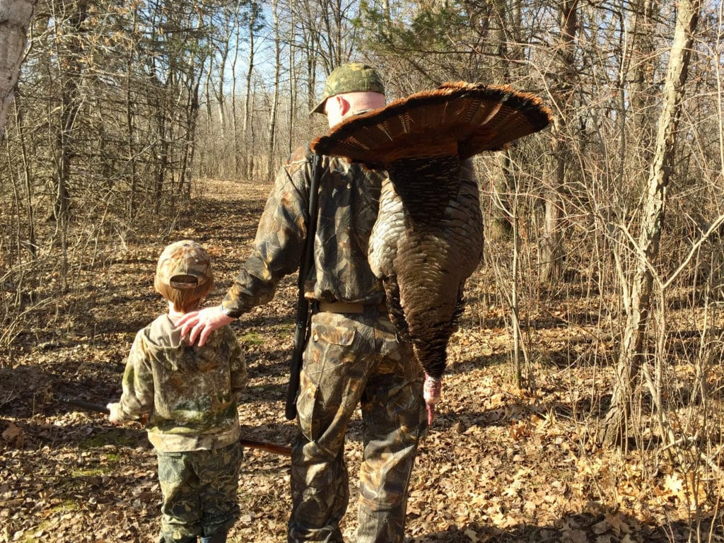 A hunter and son with a wild turkey
